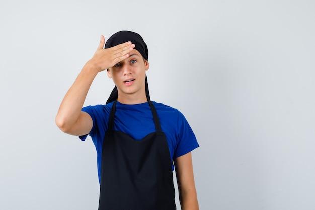 Junger kochmann im t-shirt, schürze mit hand auf der stirn und vergesslicher blick, vorderansicht.