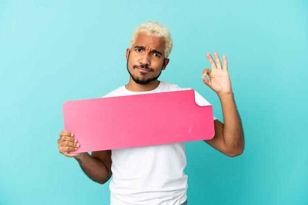 Junger kolumbianischer gutaussehender mann isoliert auf blauem hintergrund, der ein leeres plakat hält und ok-zeichen macht