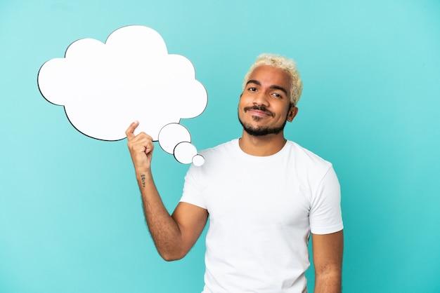 Junger kolumbianischer gutaussehender mann isoliert auf blauem hintergrund, der eine denkende sprechblase hält