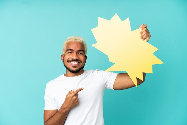 Junger kolumbianischer gutaussehender mann isoliert auf blauem hintergrund, der eine leere sprechblase hält und darauf zeigt