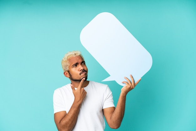 Junger kolumbianischer gutaussehender mann isoliert auf blauem hintergrund, der eine leere sprechblase hält und denkt