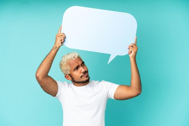 Junger kolumbianischer gutaussehender mann isoliert auf blauem hintergrund, der eine leere sprechblase hält und mit traurigem ausdruck