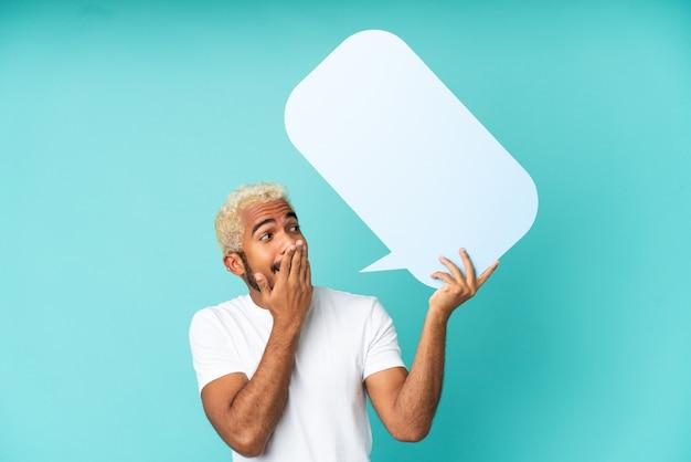 Junger kolumbianischer gutaussehender mann isoliert auf blauem hintergrund, der eine leere sprechblase mit überraschtem ausdruck hält