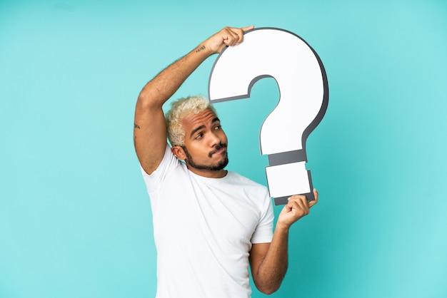 Junger kolumbianischer gutaussehender mann isoliert auf blauem hintergrund mit einem fragezeichen-symbol