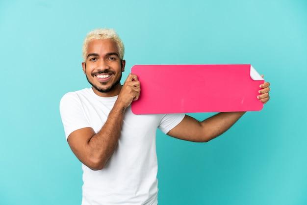 Junger kolumbianischer gutaussehender mann isoliert auf blauem hintergrund mit einem leeren plakat