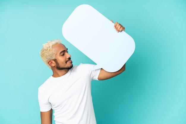 Junger kolumbianischer gutaussehender mann isoliert auf blauem hintergrund mit einer leeren sprechblase