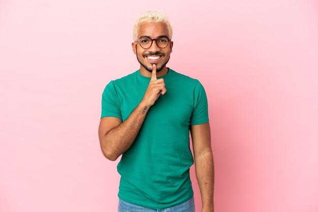 Junger kolumbianischer gutaussehender mann isoliert auf rosa hintergrund, der ein zeichen der stille zeigt, die geste finger in den mund steckt