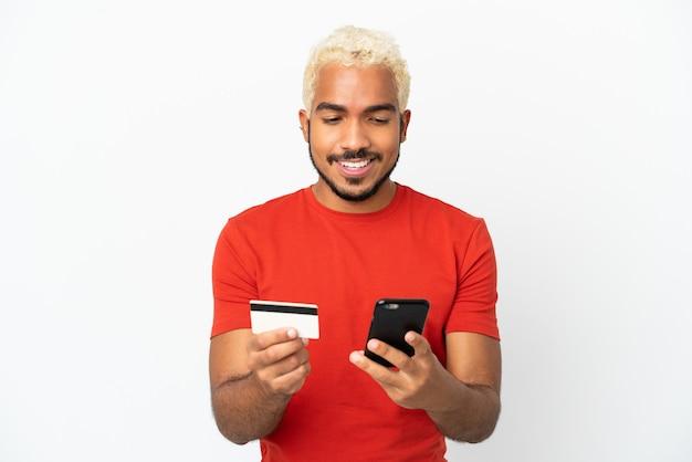 Junger kolumbianischer gutaussehender mann isoliert auf weißem hintergrund, der mit dem handy mit einer kreditkarte kauft