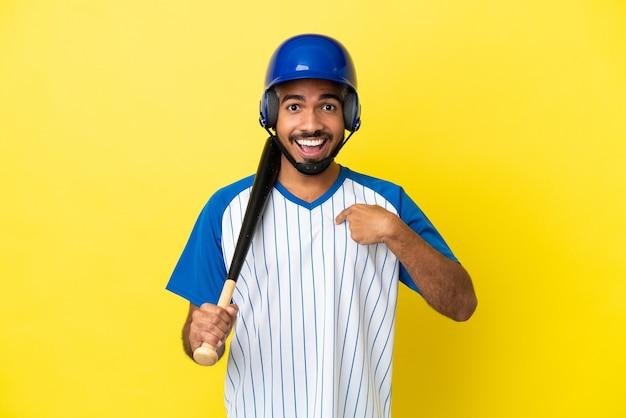 Junger kolumbianischer lateinischer mann, der baseball isoliert auf gelbem hintergrund mit überraschtem gesichtsausdruck spielt