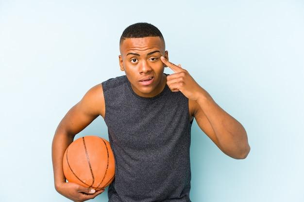 Junger kolumbianischer mann, der basketball isoliert spielt, zeigt eine enttäuschungsgeste mit zeigefinger