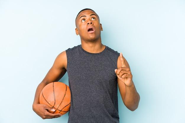 Junger kolumbianischer mann, der basketball spielt, der oben mit geöffnetem mund zeigt.