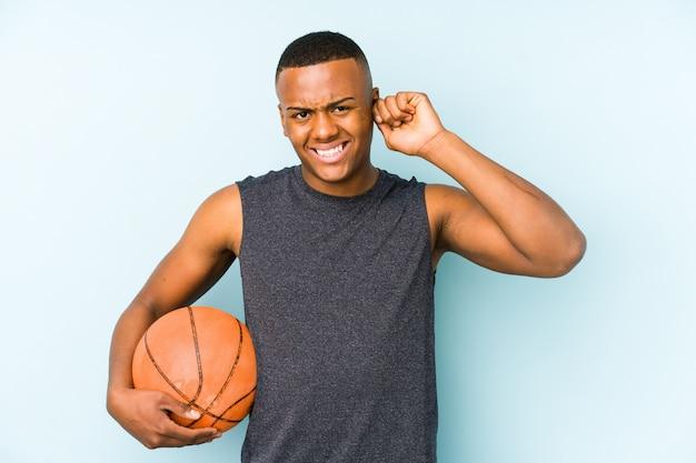 Junger kolumbianischer mann, der basketball spielt, der ohren mit händen bedeckt.