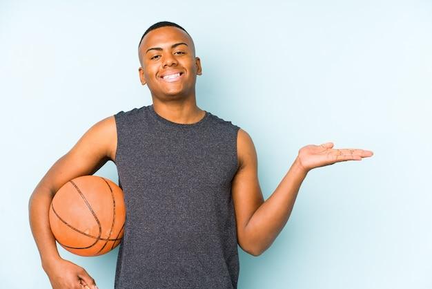 Junger kolumbianischer mann, der basketball spielt, isoliert, einen kopienraum auf einer handfläche zeigend und eine andere hand auf taille haltend.