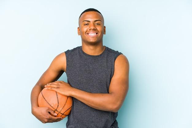 Junger kolumbianischer mann, der basketball spielt, isoliert lachend und spaß habend.