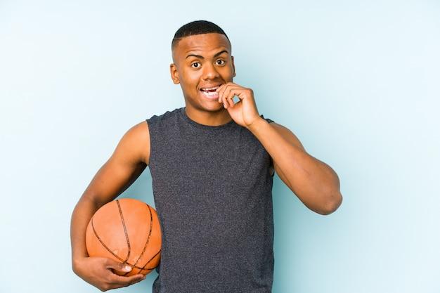 Junger kolumbianischer mann, der basketball spielt, isolierte beißende fingernägel, nervös und sehr ängstlich.