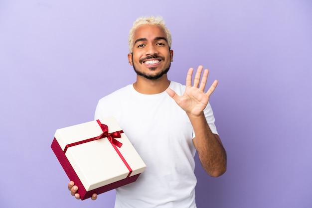 Junger kolumbianischer mann, der ein geschenk auf lila hintergrund hält, das fünf mit den fingern zählt