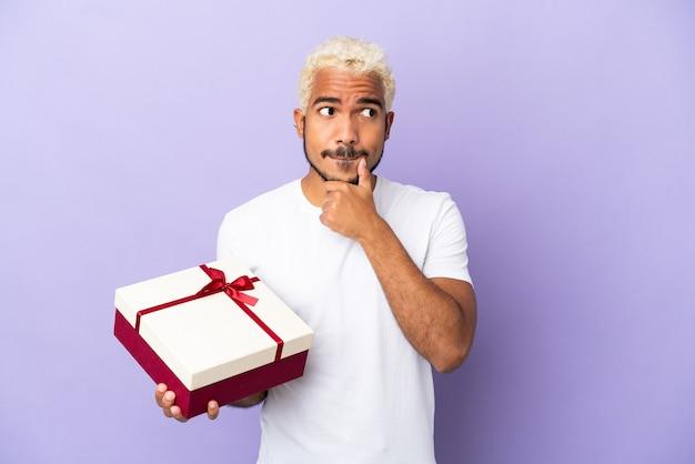 Junger kolumbianischer mann, der ein geschenk auf violettem hintergrund hält und zweifel hat und denkt