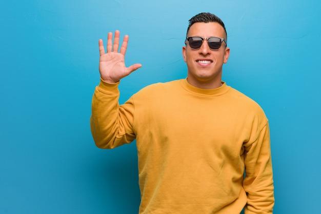 Junger kolumbianischer mann, der nr. fünf zeigt