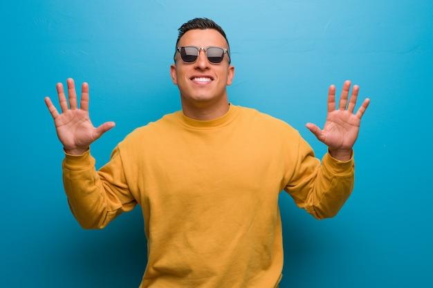 Junger kolumbianischer mann, der nr. zehn zeigt