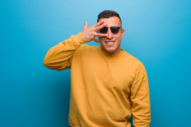 Junger kolumbianischer mann gleichzeitig verlegen und lachend