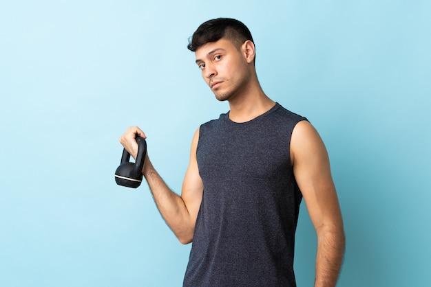 Junger kolumbianischer mann lokalisiert auf blau, das gewichtheben mit kettlebell macht