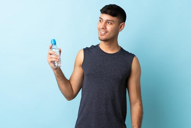 Junger kolumbianischer mann lokalisiert auf blau mit sportwasserflasche