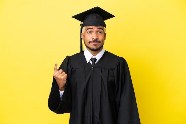 Junger kolumbianischer mann mit universitätsabschluss isoliert auf gelbem hintergrund, der mit dem zeigefinger zeigt, eine großartige idee
