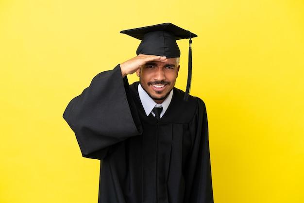 Junger kolumbianischer mann mit universitätsabschluss isoliert auf gelbem hintergrund, der mit der hand weit weg schaut, um etwas zu suchen?