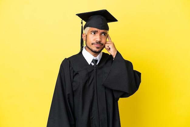 Junger kolumbianischer mann mit universitätsabschluss isoliert auf gelbem hintergrund mit zweifeln und verwirrendem gesichtsausdruck
