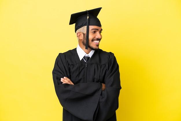 Junger kolumbianischer mann mit universitätsabsolvent isoliert auf gelbem hintergrund, der seitlich schaut