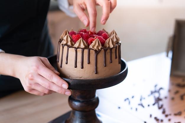 Junger konditor, der einen köstlichen hausgemachten schokoladenkuchen mit früchten in der küche kocht
