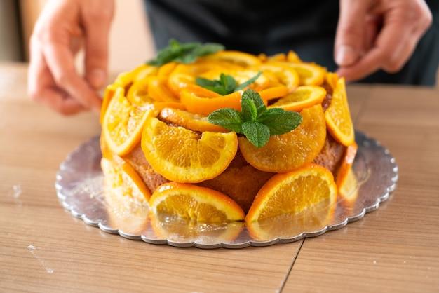 Junger konditor, der einen orangenkuchen mit geschnittenen orangen kocht