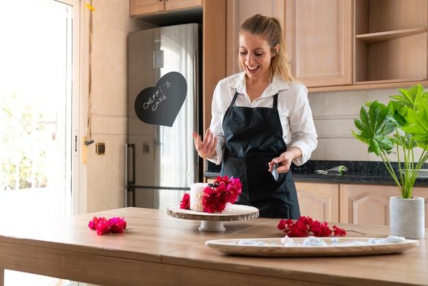 Junger konditor, der einen traditionellen roten samtkuchen in der küche kocht
