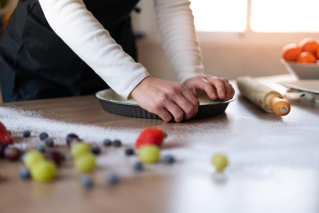 Junger konditor, der in der küche einen süßen kuchen kocht