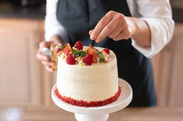Junger konditor, der in der küche einen traditionellen roten samtkuchen kocht