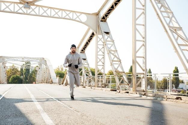 Junger konzentrierter sportler, der morgens über die brücke joggt