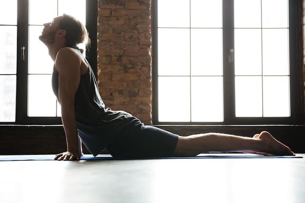 Junger konzentrierter sportler, der muskeln auf der fitnessmatte streckt
