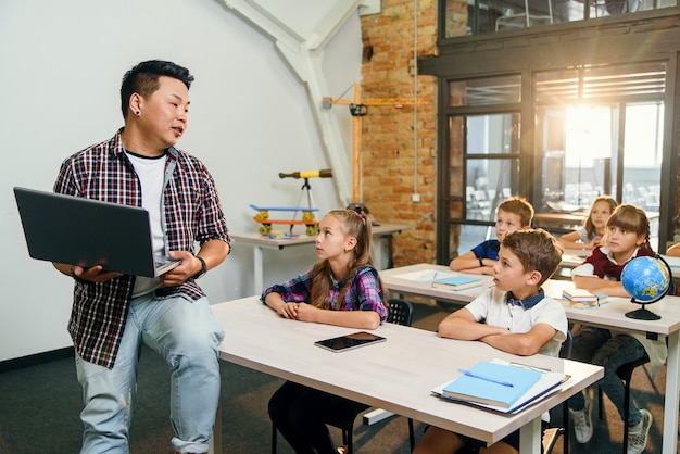 Junger koreanischer männlicher lehrer, der auf schreibtisch mit laptop sitzt und unterricht für sechs grundschüler gibt.