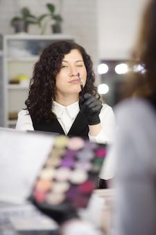 Junger kosmetiker, der spaß während der arbeit in einem schönheitssalon hat.