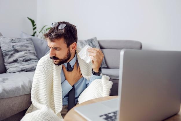 Junger kranker geschäftsmann, der taschentuch hält und hustet, während er zu hause sitzt und laptop verwendet.