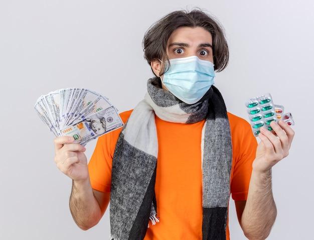 Junger kranker mann, der schal und medizinische maske trägt, die pillen und bargeld auf weiß isoliert halten