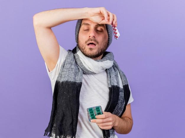 Junger kranker mann, der wintermütze mit schal hält, der pillen hält und arm auf stirn lokalisiert auf purpur setzt