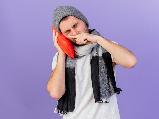 Junger kranker mann, der wintermütze mit schal hält, der wärmflasche auf wange lokalisiert auf purpur hält