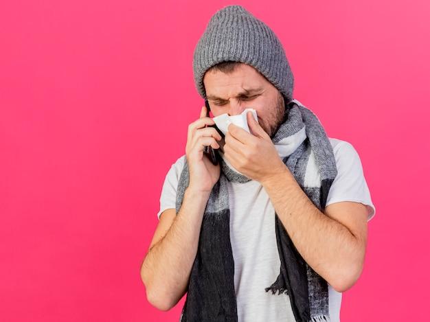 Junger kranker mann, der wintermütze mit schal trägt, spricht am telefon und wischt nase mit serviette lokalisiert auf rosa