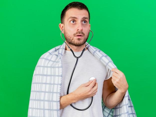 Junger kranker mann in plaid gewickelt, der seinen eigenen herzschlag mit dem auf grün isolierten stethoskop trägt und lauscht
