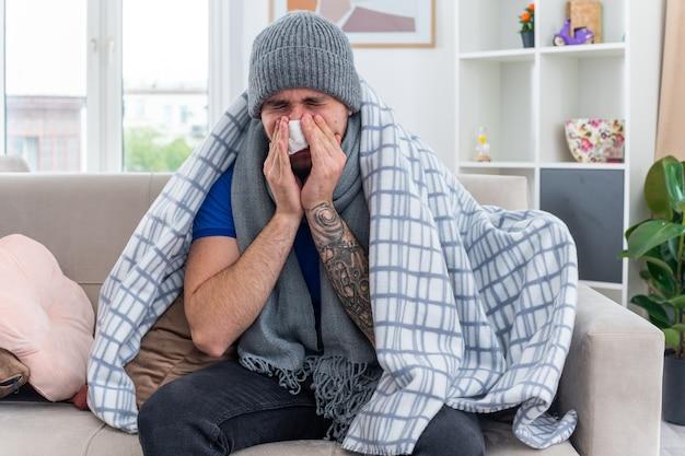 Junger kranker mann mit schal und wintermütze, der in eine decke gehüllt ist, sitzt auf dem sofa im wohnzimmer und wischt sich mit geschlossenen augen die nase mit einer serviette ab