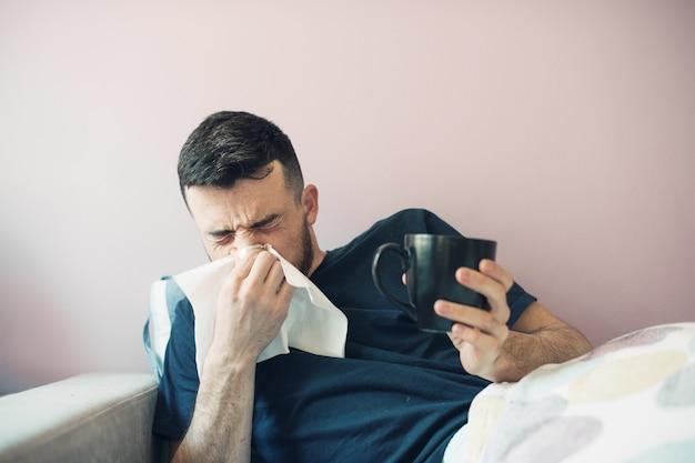 Junger kranker mann mit taschentuch. der typ liegt mit einer decke im bett und niest und bedeckt seine nase mit einer serviette. in der anderen hand hält eine tasse.