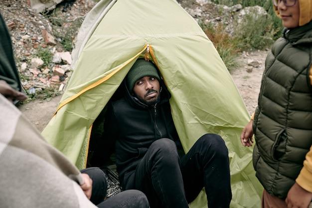Junger kranker mann sitzt im zelt unter anderen flüchtlingen