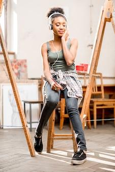 Junger kreativer afrikanischer ethnizitätsstudent, der während der pause im universitätsstudio zum malen auf dem stuhl sitzt