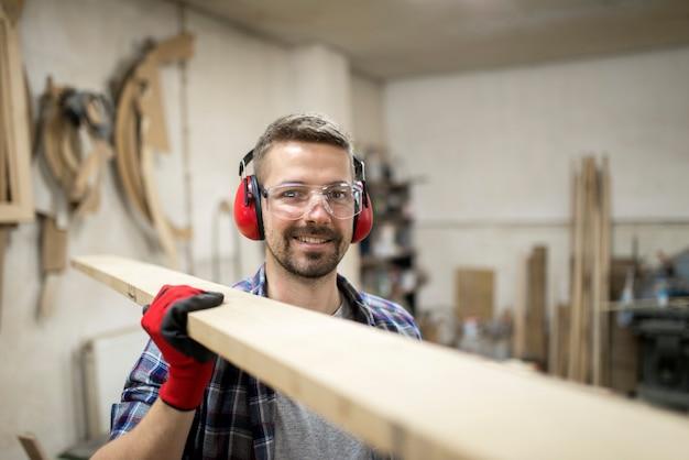 Junger kreativer arbeiter schreiner, der plankenholzmaterial in der tischlerwerkstatt hält
